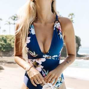 Model on the beach wearing a Blue Floral Strappy One Piece Swimsuit